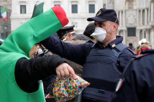 A police officer wearing a protective face mask stands next to a carnival reveller at Venice Carnival