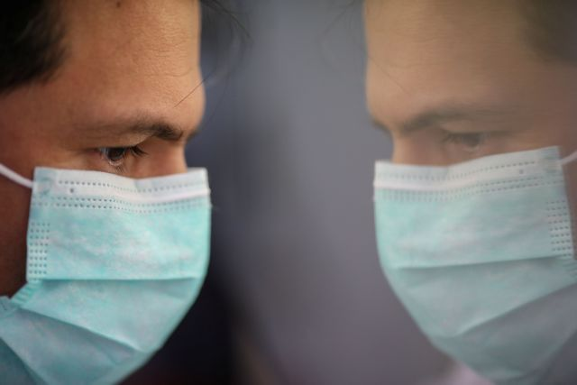 Scientist is reflected as he works on cells that produce antibodies against the coronavirus disease (COVID-19), in a university lab in Athens