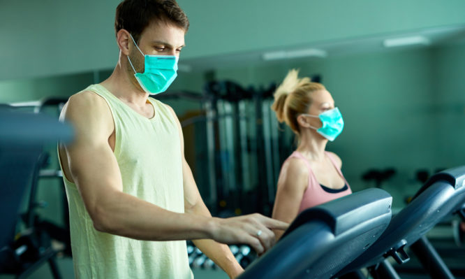 Athletic couple with protective face mask exercising on treadmill at the gym.